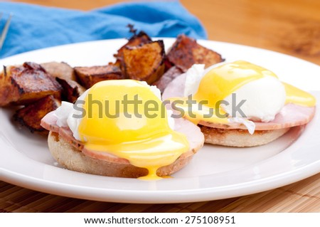 eggs benedict with farm fresh eggs and ham and fried potatoes - stock photo