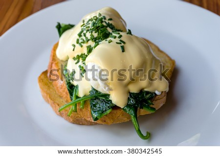 Eggs Benedict with spinach on toast. Poached egg on toast with spinach and chives on white plate. Healthy breakfast. Selective focus, shallow dof - stock photo