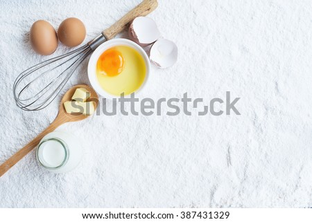 eggs butter milk bottle whisk on wheat flour background, basic baking background.  - stock photo