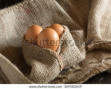 Eggs covered by a burlap sack over a dark background
