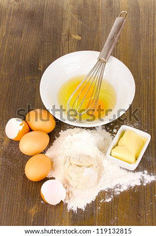 Eggs, flour and butter close-up on wooden table - stock photo
