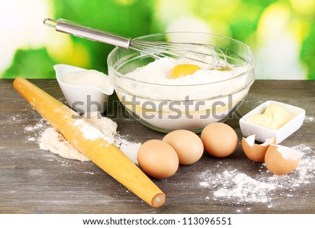 Eggs, flour and butter close-up on wooden table on natural background - stock photo