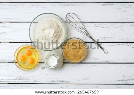Eggs, flour, milk, brown sugar with whisk on white wooden table from above.