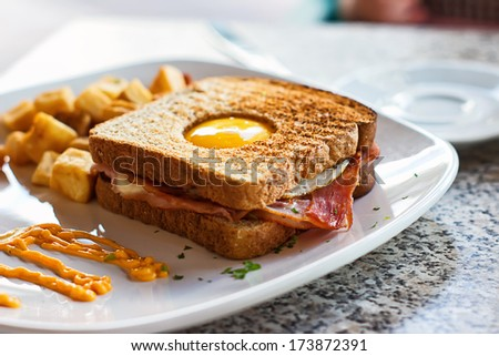 Eggs in a Basket Breakfast of egg, bacon, toast and hash browns - stock photo
