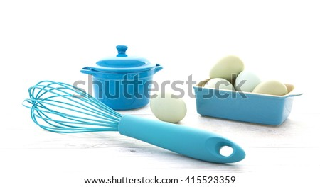 Eggs in a blue bowl with a wisk on a rustic white wood table top shot from above - stock photo