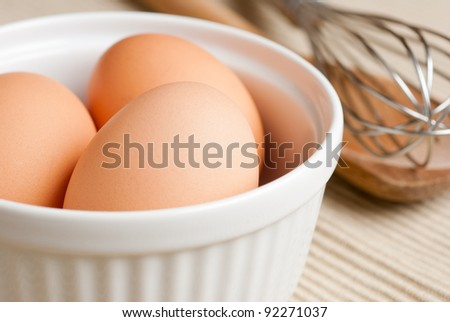 Eggs in a bowl with a metal whisk and wooden spoon. - stock photo