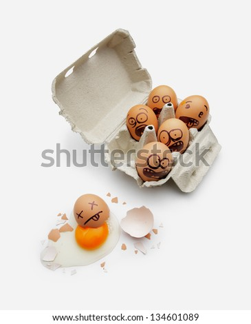 Eggs in a box are scared of dead friend - stock photo