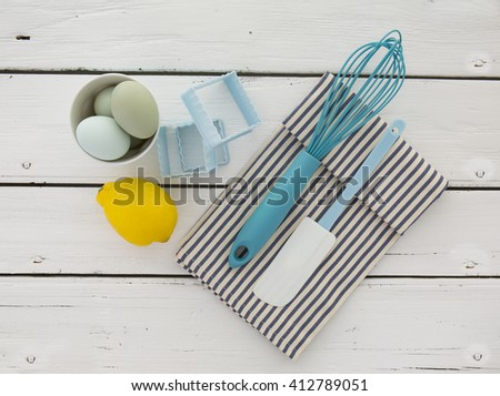 Eggs in a ceramic bowl with a whisk and lemon on a rustic white painted wood table top shot from above - stock photo