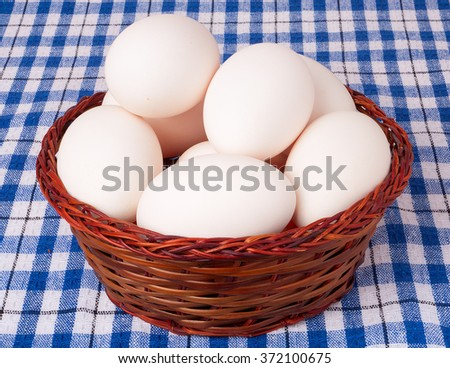 eggs in a wicker basket on a blue checkered background.