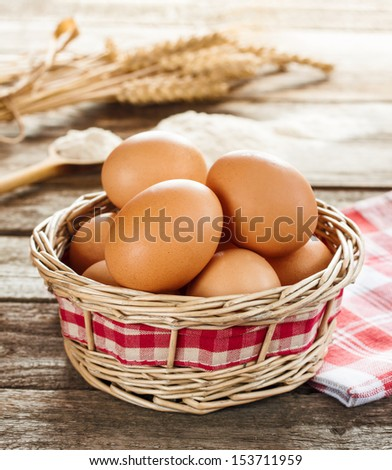 Eggs in a wicker basket on an old vintage planked wood table, wheat bunch and flour as background. Rural or rustic kitchen still life. - stock photo