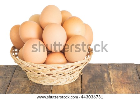 eggs in basket on old wooden and white background - stock photo