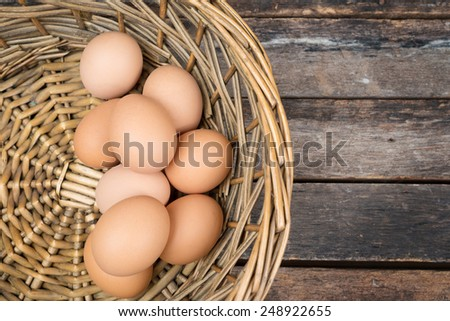eggs in basket on wooden background. - stock photo