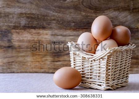 eggs in basket over wood - stock photo