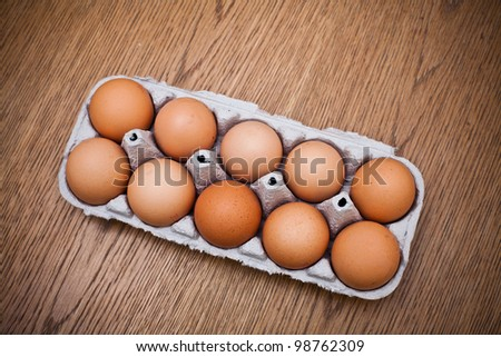 Eggs in box on a wooden table - stock photo