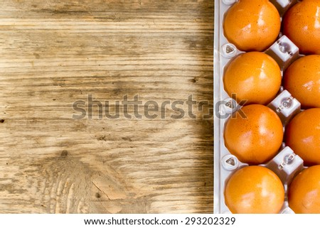 Eggs in box on a wooden table. Copy space to right. - stock photo