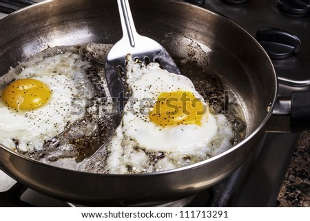 Eggs in frying pan being cooked by bacon grease with spatula - stock photo