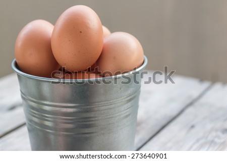 eggs in metallic bucket on wood - stock photo