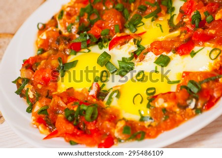 eggs in sauce of tomatoes, peppers, and onions - stock photo