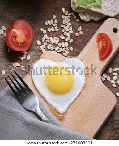 eggs in the shape of a heart on a wooden board - stock photo