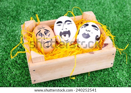 Eggs in wooden box on green background