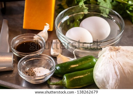 Eggs, jalapenos, kosher salt, cheddar cheese cilantro, soy sauce and onion ingredients sitting on a silver pan - stock photo