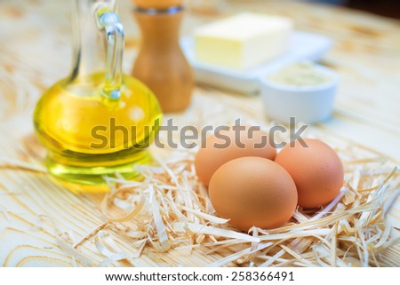 Eggs, oil and food ingredients on wooden background - stock photo