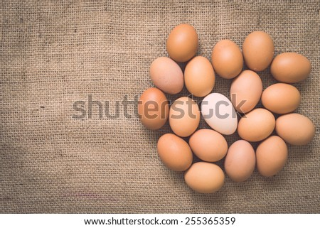 Eggs on old crumpled burlap background with retro filter effect  - stock photo