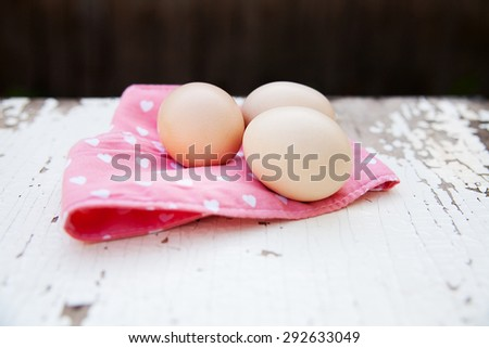 Eggs on pink tablecloth over old cracky white wooden background.  - stock photo