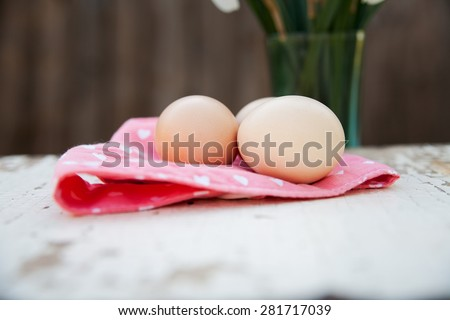Eggs on pink tablecloth over white wooden background and vase - stock photo