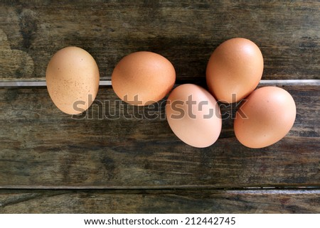 Eggs on wooden table background - stock photo