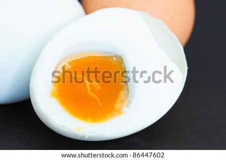 Eggs Salted cut in half on black background - stock photo