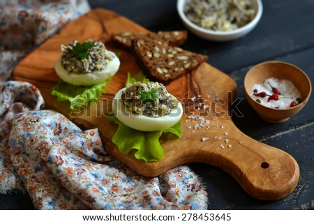 eggs stuffed mushrooms at olive Board on dark wooden surface - stock photo