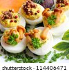 Eggs stuffed with boiled egg yolk, fried onions and mushrooms - stock photo