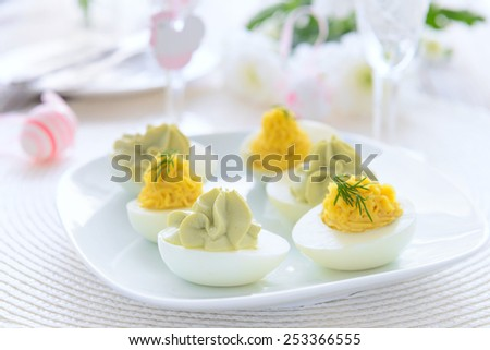 Eggs stuffed with cheese and avocado mousse on Easter table - stock photo