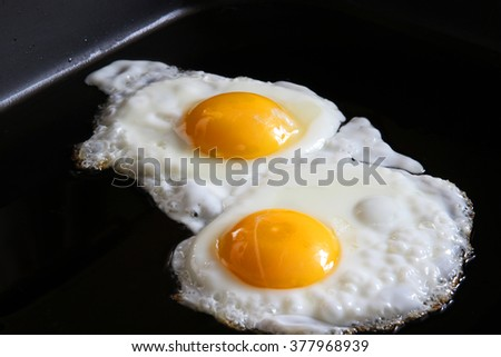 eggs sunny side up on black greasy grill closeup