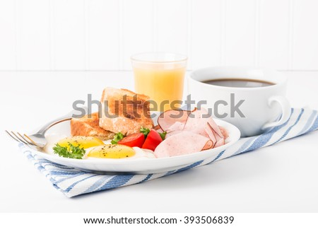 Eggs sunny side up served with ham, coffee and toast. - stock photo