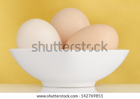 Eggs,Three eggs in the bowl on a yellow background. - stock photo
