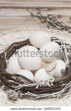 Eggs. White eggs in nest on a brown wooden table. Easter decoration. Done with vintage retro filter. Macro, selective focus - stock photo