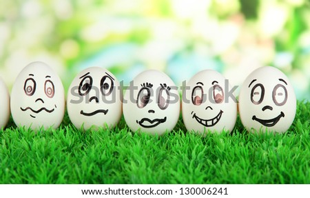 Eggs with funny faces on grass on bright background - stock photo