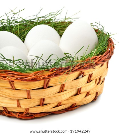 eggs with green grass in the basket isolated on white - stock photo