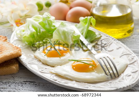 eggs with green salad on dish - stock photo