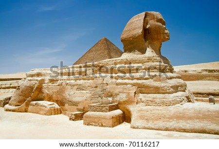 egiptian sphinx in desert near old pyramid - stock photo