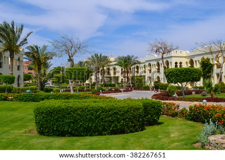 Egypt:16 April 2015, The green meadow with trees in tropical garden villas