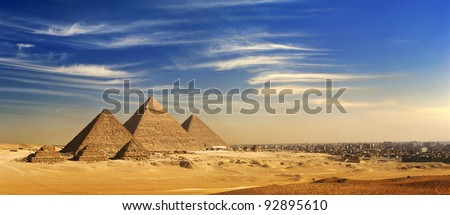 Egypt. Cairo - Giza. General view of pyramids and cityskape from the Giza Plateau (on front side: three pyramids known as Queens' Pyramids; next: the Pyramid of Menkaure, Khafre and Chufu) - stock photo