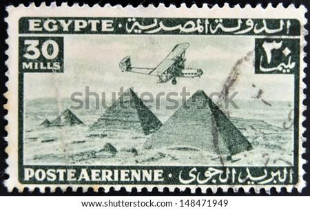 EGYPT - CIRCA 1946: stamp printed in Egypt shows plane over Pyramids at Giza, circa 1946  - stock photo