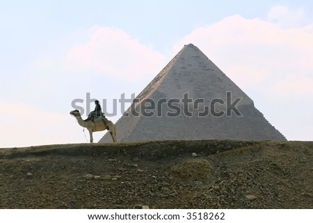 Egyptian Camel rider in front of great pyramid of Cairo - stock photo