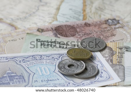 Egyptian coins and notes on map of Middle East, selective focus - stock photo