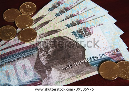 Egyptian coins and 100 pound notes. - stock photo