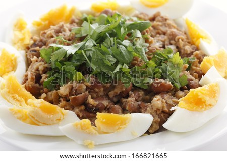 Egyptian foul - or ful - medammes on a plate garneshed with slices of hard-boiled egg and flat-leaf parsley. Foul is probably Egypt's most famous food. - stock photo