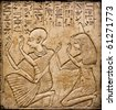 Egyptian hieroglyphs and human figures engraved on stone - stock photo